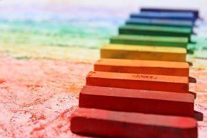 verschieden farbige Malkreiden die auf einem bemalten Papier in Regenbogenfarben aneinander gereiht sind