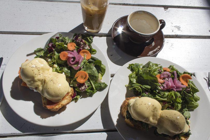 auf einem Holztisch stehen ein Latte Macchiato, ein Milchkaffee und zwei Teller mit zwei Benedict Eier auf Brot und daneben eingroßer Salat