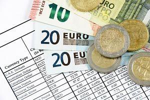Auf einer Liste mit verschiedenen Währungen liegen zwei 20€, ein 10 ein 5€ Schein und zwei 2€ und eine 10 Cent Münze