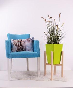 links ein moderner hellblauer Sessel mit einem hellen Kissen und rechts ein Holzgestell mit einem hellgrünen Blumentopf und hohen Gräsern darin