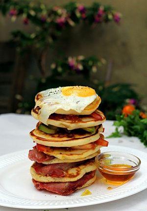 ein großer weisser Teller mit einem Pancaketurm oben drauf ein Spiegelei und zwischen den Törtchen Schinken und Tomate und daneben ein kleines Glasschüsselchen mit Ahornsirup