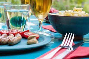 auf einem Tisch mit blauer Tischdecke zwei gefüllte Biergläser, eine Schüssel mit Kartoffelsalat, ein Glas Wasser, auf einer roten Serviette eine Gabel und ein Messer und ein Teller mit Würstchen und Tomatenscheiben