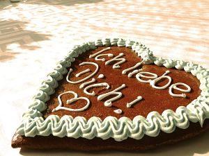 ein großes Lebkuchenherz auf dem mit weißem Fondant Ich liebe Dich steht mit einem Ausrufezeichen und einem Herz darunter