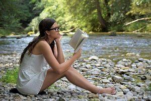 eine junge Frau mit langen Haaren, schwarzer Brille und einem weissen kurzen Kleid sitzt am Ufer eines Flusses und liest ein Buch