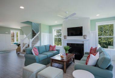 Wohnzimmer einer Immobilie hinten im Bild eine Treppe mit weissem Geländer die ins erste Stockwerk führen, rechts ein Kamin und in der Mitte eine Sofasitzecke mit zwei grünen Viersitzern und einem kleinen Holztisch in der Mitte, an jeder Wand zwei Fenter aus denen man grüne Bäume sieht