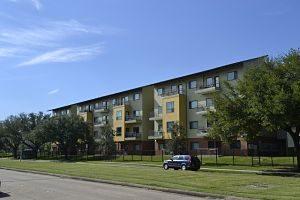 ein Wohnblock in einer Wohnsiedlung, rechteckig in bei und gelb mit viel Grünfläche drum herum und einem blauem Auto davor