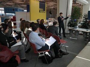 offener Raum in dem mehrere Personen auf roten Stühlen sitzen und einem Herrn der vorne im Anzug ein Mikrofon spricht