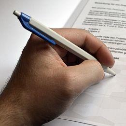 linke männliche Hand die gerade mit einem Kugelschreiber auf einem Betrag ansetzt um zu unterschreiben