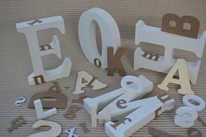 auf einem gewelltem Pappkarton liegen und stehen verschieden große Buchstaben