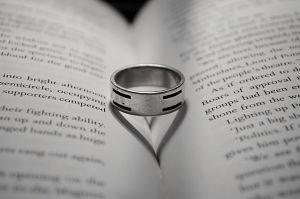ein offenes Buch mit einem silbernen Ring in der der Mitte dessen Schatten ein Herz ist