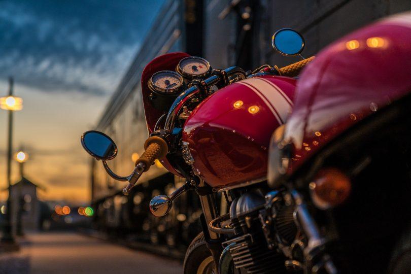 ein rotes Motorrad mit einem weissen Streifen in der Mitte das bei Dämmerung in der Straße einer Stadt geparkt ist