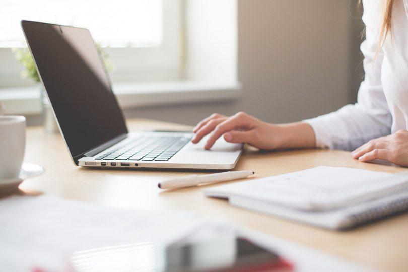 hölzerner Schreibtisch mit einem Laptop, einem Bleistift, mehrere Unterlagen und eine weibliche Hand die etwas am computer macht