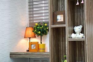 rechts ein Holzregalt mit einem Bilderrahmen und einem weissen Teddybären, links ein mittelgroßer schränk auf dem eine orangene kleine Stehlampe, ein Bilderrahmen und ein kleiner Zitronenbaum steht