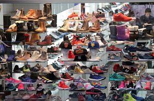 das Schaufenster eines Schuhladens in dem mitndestens 30 verschiedenen Schuhe ausgestellt sind und zwischen Turnschuhen und Winterstiefeln sieht man einige Baseballmützten