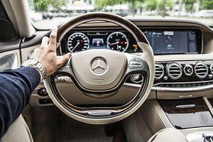 Fahrerseite eines Mercedes Benz mit beiger Innenausstattung, ein Mann hat seine linke Hand am Lenkrad, silberne Uhr und blauer Pullover