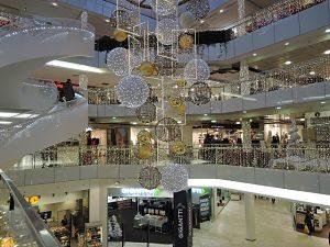 ein Einkaufszentrum von innen das mit weissen, goldenen und silbernen Weihnachtskugeln dekoriert ist