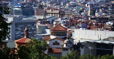 Blick auf Barcelona vom Gaudi Park aus, im Vordergrund grüne Bäume und danach Gebäude so weit das Auge reicht