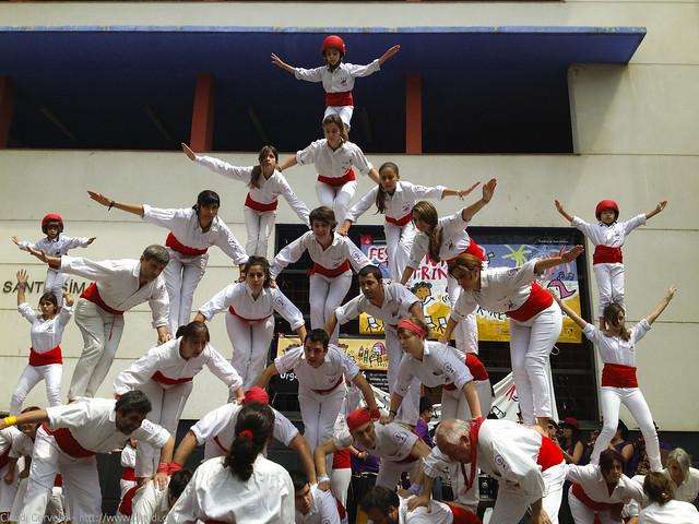Die Falcons von Barcelona in einer spektakulären Menschenpyramide alle weiß gekleidet mit roten Gürteln