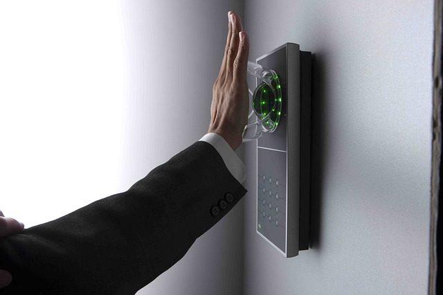 eine Person die ihre Hand vor einen Handvenenerkennungsgerät hält um eine Türe zu öffnen