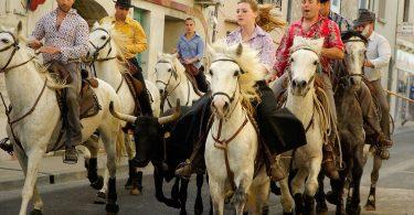 vier Männer und zwei Frauen die auf weißen und braunen Pferden durch die Straße reiten