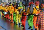ein Faschingsumzug die Clowns laufen in einer Reihe mit ihren Musikinstrumenten alle mit orangnen Pullovern und grünen, roten oder gelben Hosen