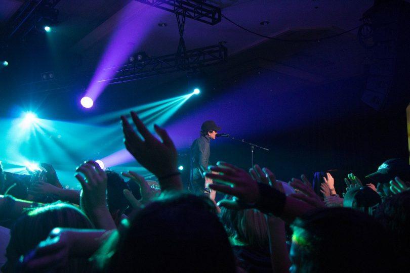 im Vordergrund eine Menschenmenge und auf der Bühne ein schwarzbekleideter Sänger mit Mütze türquises und Lianes Scheinwerferlicht
