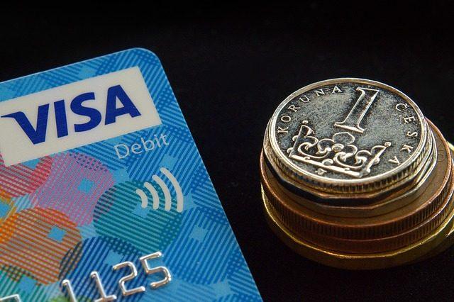 links ist die hälfte einer Visa Kreditkarte zu sehen und rechts daneben ein Turm aus tschechischen Münzen