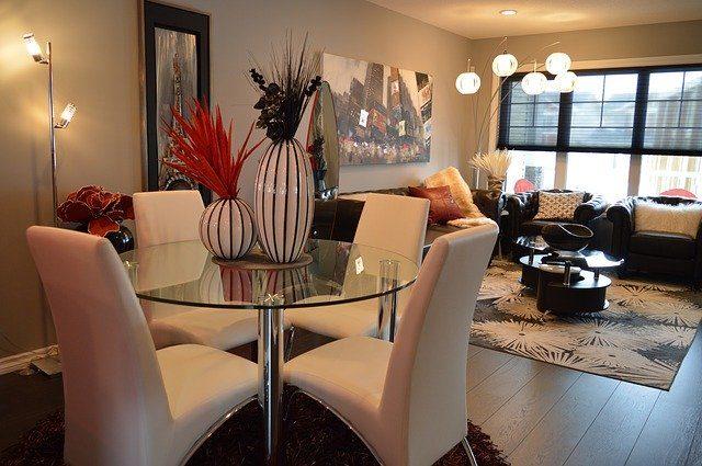 ein Ess-Wohn Zimmer, runder Glastisch mit vier weißen gepolsterten stuhlen und im Hintergrund eine Sitzecke