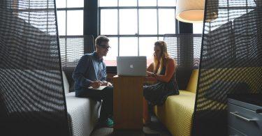 ein junger mann mit brille und eine junge Frau mit blonden langen haaren sitzen sich auf zwei Sofas gegenüber und sehen sich etwas auf einem Laptop an der zwischen ihnen auf einem kleinen Holztisch steht