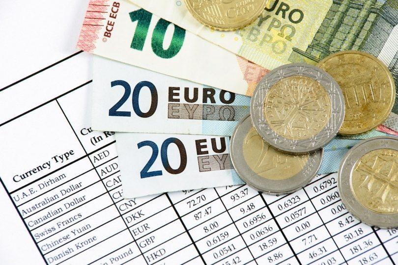 in einem Fächer liegen zwei zwanzig euro scheine ein zehn euro Schein und ein fünf euro schein mit Münzen darauf auf einer Tabelle mit Wechselkursen verschiedener Währungen