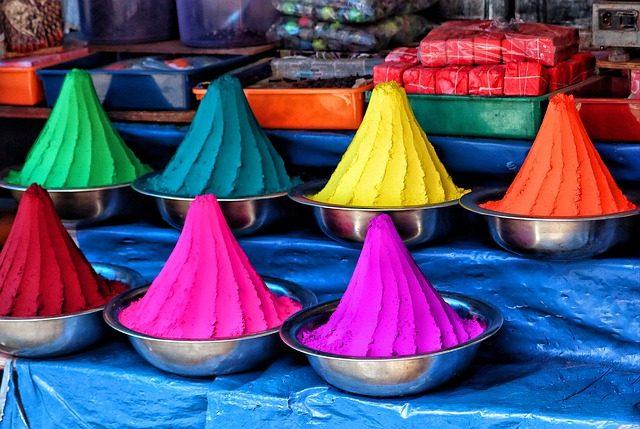 mehrere metalschüßeln mit verschiedenfarbigen Pulver darin aufgetürmt, grün, blau, gelb, orange, rosa, rot, lila