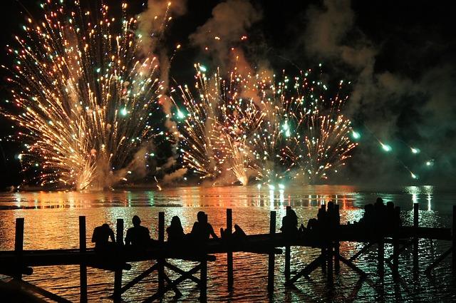 Mehrere Personen die auf einem Steg überm Wasser sitzen und ein Feuerwerk bestaunen