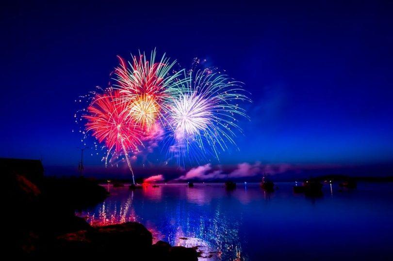 Sicht auf ein farbenfrohes Feuerwerk bei nacht über dem Meer