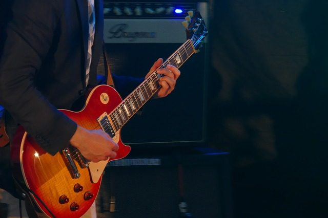 ein Mann der auf einer rot-orangenen E-Guitarre spielt
