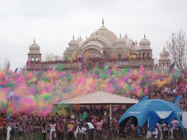 ein Hindutempel mit einer Menschenmenge drum herum und in der Luft schweben verschiedenfarbige Pulver die die Leute in die höhe geworfen haben