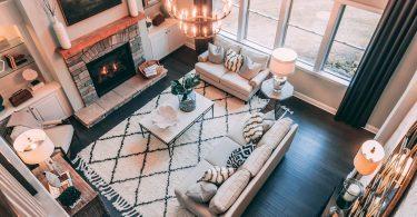 ein Wohnzimmer von oben fotografiert mit einem großen Teppich in der Mieter darauf ein beiges Sofa ein kleiner weißer viereckiger Tisch dahinter ein verschlossener Kamin und rechts Fenster über die ganze Wandbreite
