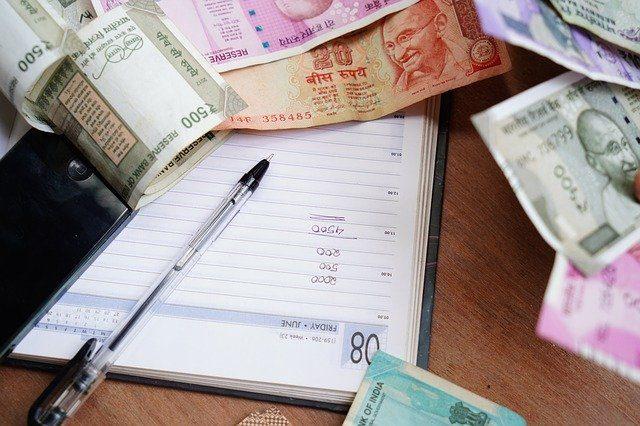 ein offenes Buch mit einem Kugelschreiber darauf in dem mehrere zahlen untereinander notiert wurden und drum herum liegen verschiedene indische Geldscheine