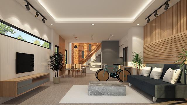 das Wohn-Esszimmer eines modernen Fertigahauses mit einem Mamorblock als Wohnzimmertisch und zwei Bambusfahrräder neben einem dunkelblauem Sofa