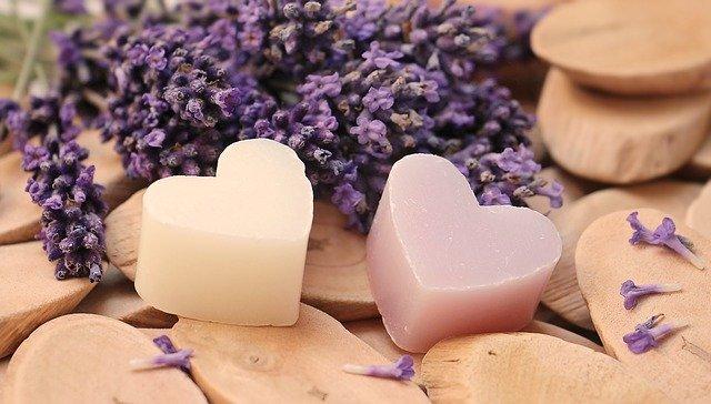 ein weißes und ein rosanes herzförmiges Seifenstück auf holz und dahinter Lavendelblüten