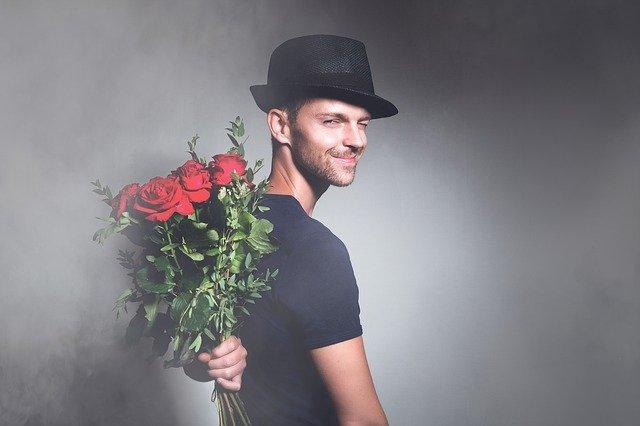 ein junger Mann im schwarzen T-Shirt, mit schwarzem Hut auf, der seitlich steht und lächelnd und Augenzwinkern nach hinten schaut und mit der linken Hand einen Strauß roter Rosen hinterm Rücken hält