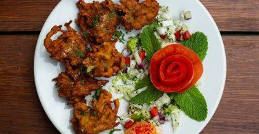 ein weißer runder Teller mit indischem Pakora auf der linken Seite und Salat mit minzblättern und einer in Rosenform geschnittene tomate