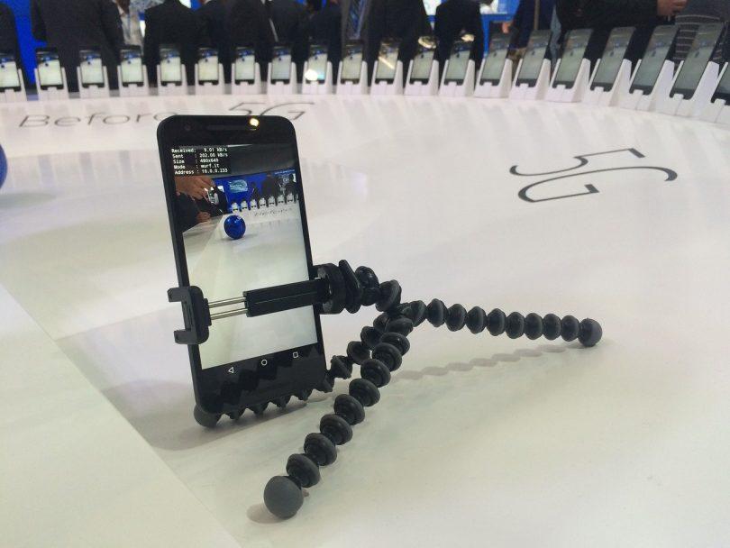 ein runder weißer Tisch auf dem %G steht in der Mitte nimmt ein Handy ein video vom Tisch und einem blauen Ball auf und um den Tisch herum sind Handys aufgestellt