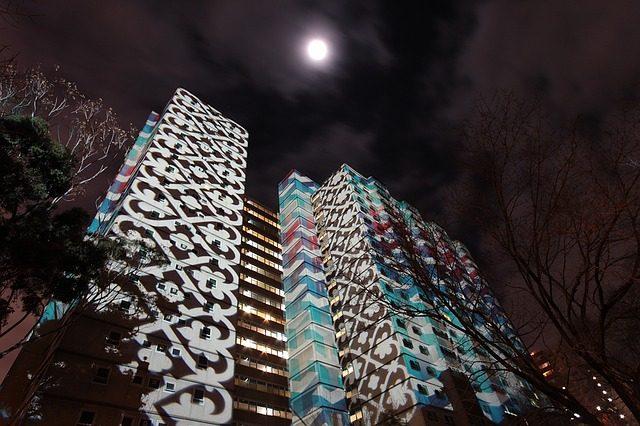 ein Hochhaus auf dem verschiedene Muster projiziert werden, es ist Nacht und genau darüber sieht man den Vollmond