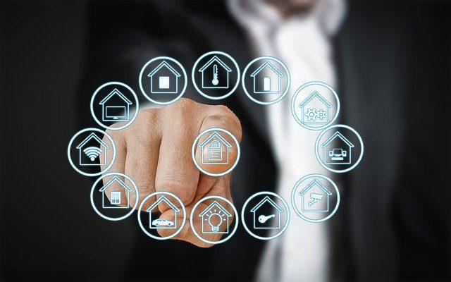 ein Mann im schwarzen Anzug und weißen Hemd der mit seinem Zeigefinger auf ein Panel deutet, das verschiedenen Funktionen eines Smart Homes anzeigt