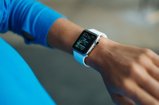 eine Person mit blauem Pullover, man sehr den Arm mit einer Smart-Watch mit weißem Armband