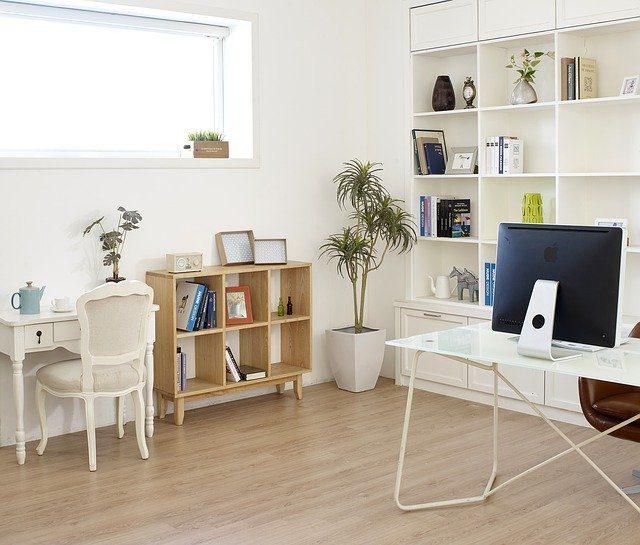 ein helles Arbeitszimmer mit einem weißen Schreibtisch auf dem ein großer schwarzer Computerbildschirm von hinten zu sehen ist dahinter ein offenes Bücherregal