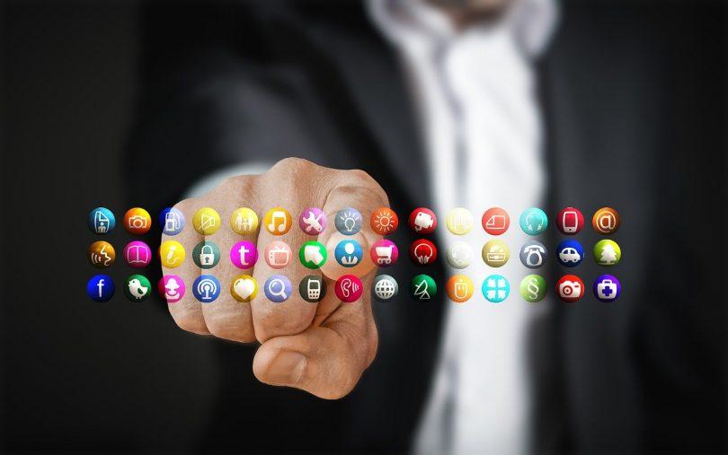 ein man in schwarzem Anzug und weißen Hemd der mit seiner rechten Hand auf ein panel mit verschiedenen Apps zeigt