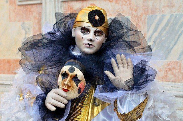 ein Junge der als trauriger Clown verkleidet ist und eine venezianische Maske in der Hand hält