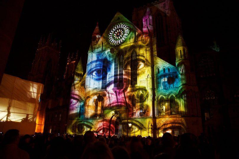 Projektion eines Gesichts und Augen in verschiedenen Farben auf der Fassade eines großen Gebäudes