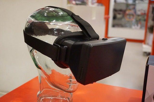 ein durchsichtiger Kopf auf einem orangenen Tisch der eine virtual reality Brille auf hat